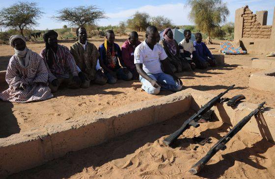 Soldados malienses rezan junto a sus fusiles en la ciudad de Gao.