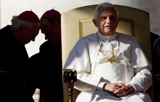 El Papa preside una audiencia en San Pedro mientras dos obispos conversan a su espalda.