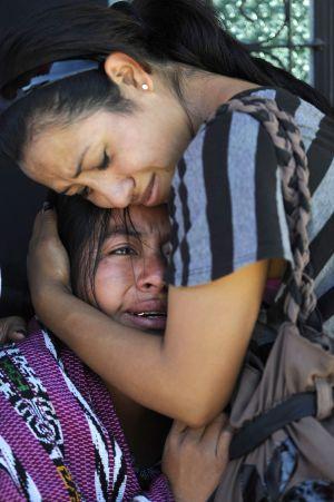 Dos mujeres lloran tras un tiroteo en Ciudad de Guatemala.