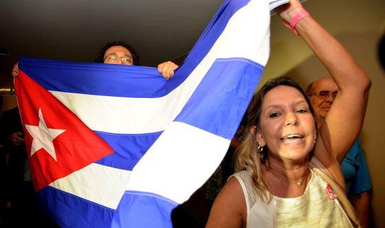 Un grupo de personas porta una bandera cubana.