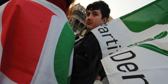 Un joven italiano lleva una bandera del Partido Democrático en un mitín de la formación.