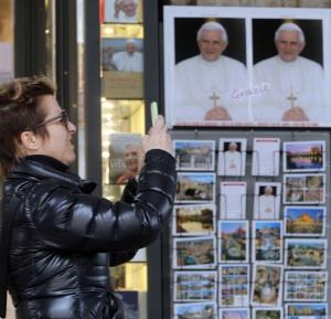 Una mujer fotografía una imagen de Benedicto XVI