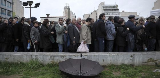 Ciudadanos esperan para recibir comida gratuita, en Atenas.