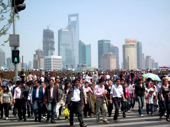 Decenas de turistas junto al río Huangpu, con el relieve de fondo del distrito financiero de Shanghái, una de las mayores ciudades chinas, el 1 de mayo de 2010.