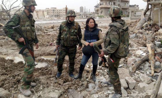 Una periodista conversa con soldados sirios entre escombros a las afueras de Damasco, en una fotografía cedida por la agencia oficial SANA.