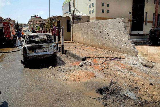 Un coche al lado de un edificio municipal alcanzado por disparos de mortero en Damasco.
