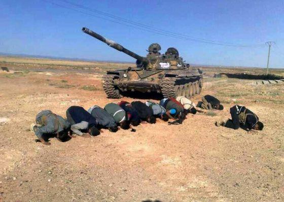 Rebeldes sirios rezan junto a un tanque en la provincia de Deraa.