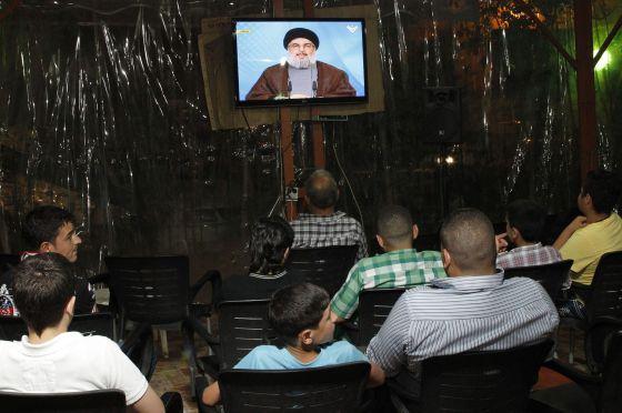 Varios hombres siguen en Beirut la alocución de Nasrala sobre Siria.