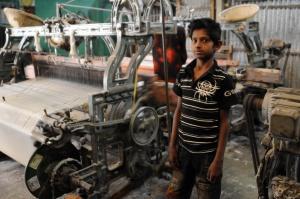 El pequeño Ahmed R. junto al telar en el que trabaja.
