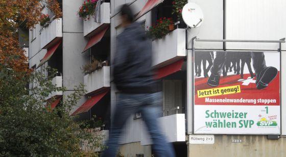 """Un transeúnte pasa ante un cartel del derechista SVPUDC que llama a """"frenar la inmigración masiva"""""""