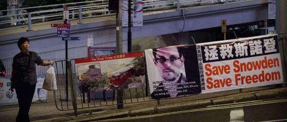 Una mujer espera para cruzar una calle junto a un cartel desplegado en apoyo a Edward Snowden en Hong Kong.