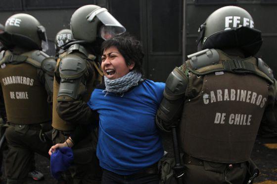 Una manifestante es detenida por la policía durante la protesta.