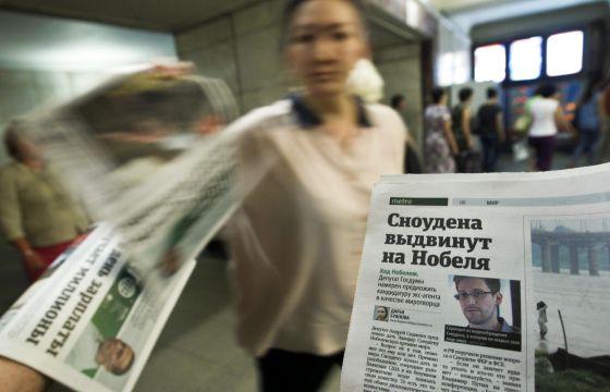 Reparto de diarios con el rostro de Snowden en el Metro de Moscú.