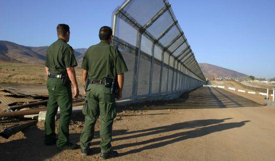 Foto de archivo sin fecha que muestra a dos policías vigilando la frontera de México y EE UU.