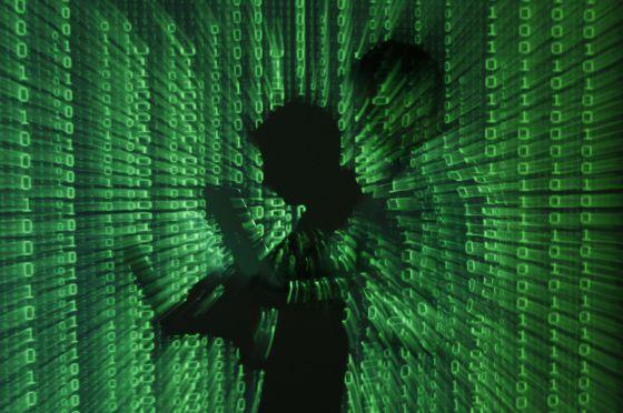 Un hombre consulta su ordenador sobre un fondo del código binario.