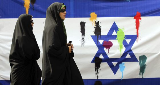 Un par de mujeres iraníes pasan delante de una bandera israelí durante una manifestación convocada para celebrar, hoy, el Día de Jerusalén.