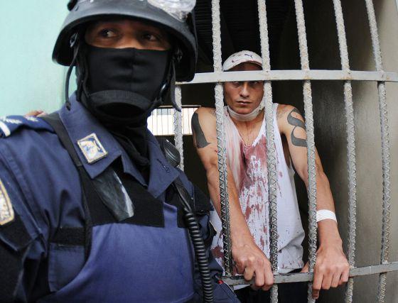 Un policía custodia a un preso herido en una prisión de Tegucigalpa.