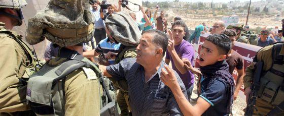 Civiles palestinos y soldados israelíes en Hebrón.