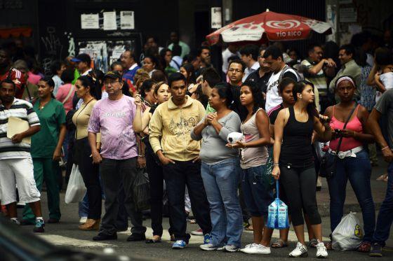 Personas esperan por el transporte público esta tarde en una calle de Caracas.