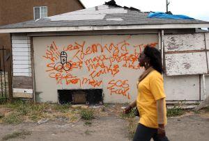 Una mujer pasa frente a una casa abandonada en Richmond.