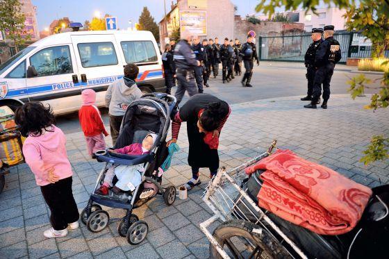 La policía francesa vigila a una familia gitana que desaloja un campamento en Roubaix el 3 de octubre.