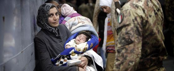 Un soldado italiano auxilia a inmigrantes rescatados a 50 km de Lampedusa.