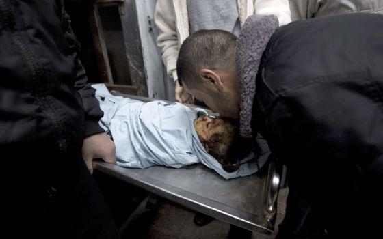 Un familiar besa el cadáver de la niña muerta en un bombardeo en Gaza.