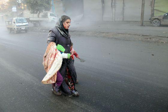 Una mujer siria y su hijo, tras un bombardeo en Alepo.
