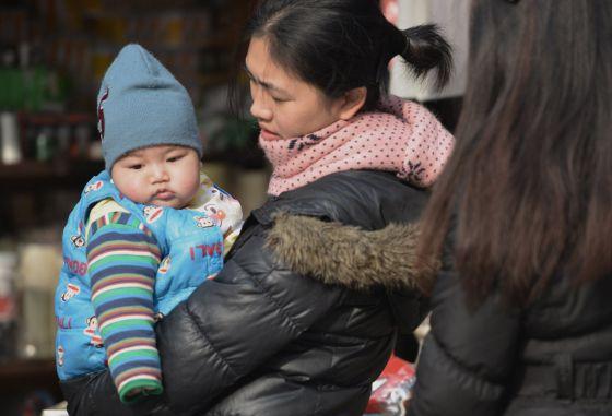 Una madre con su bebé en una calle de Shanghái.