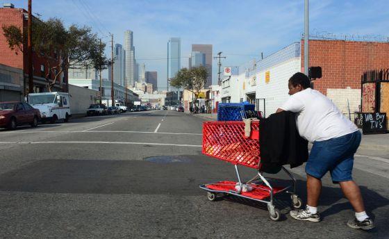 Una mujer sin techo camina por las calles del centro de Los Ángeles