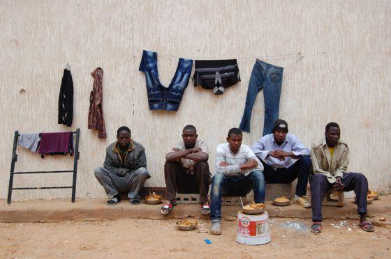 Varios inmigrantes posan en un centro de detención temporal en Trípoli.