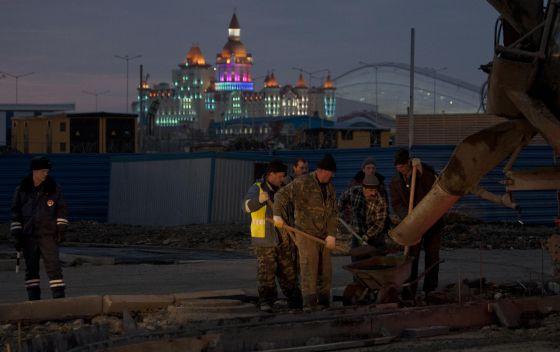 Un policía observa  a los trabajadores que ultiman los viales de acceso al Parque Olímpico.