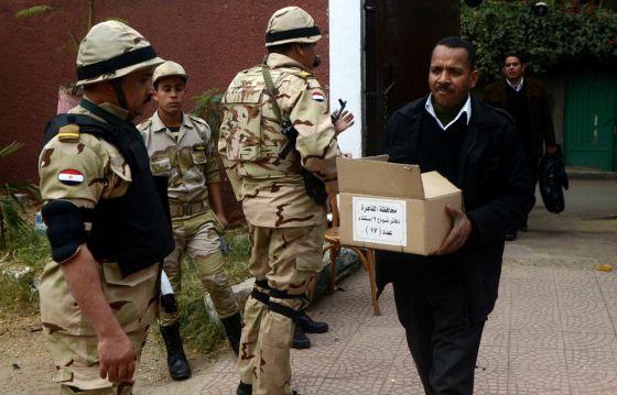 Un egipcio carga una caja con papeletas en un colegio electoral de El Cairo.