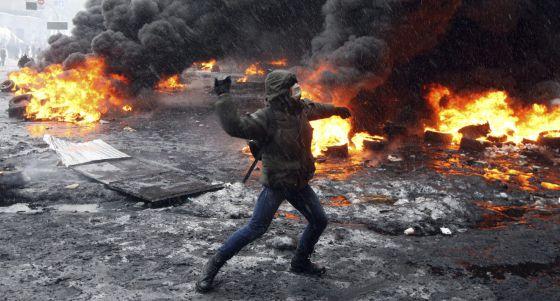 Un manifestante lanza un objeto a la policía en Kiev.