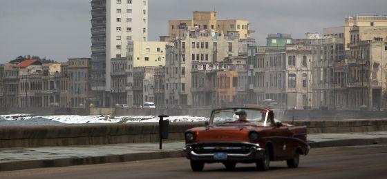Un viejo auto circula por el malecón La Habana.