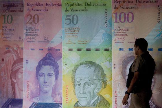 Un hombre camina frente a unos afiches de billetes venezolanos.