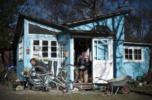 Una mujer repara su bicicleta en la entrada de su casa.