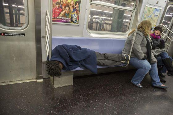 Un hombre sin hogar duerme en el metro de Nueva York.