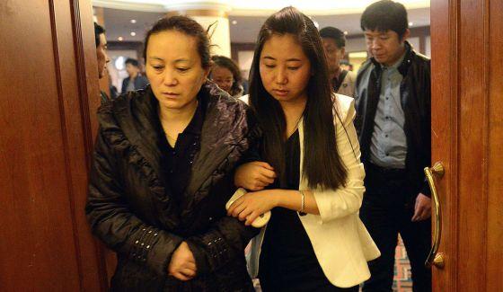 Los familiares de los pasajeros aguardan noticias. En la imagen, la madre de Lin Annan, uno de los pasajeros desaparecidos, en el aeropuerto de Pekín. G. C. H. (AFP)