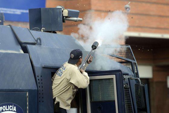Un antidisturbios dispara bombas de gas lacrimógeno.