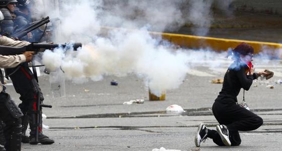 La policía nacional venezolana dispara gas lacrimógeno en Caracas.