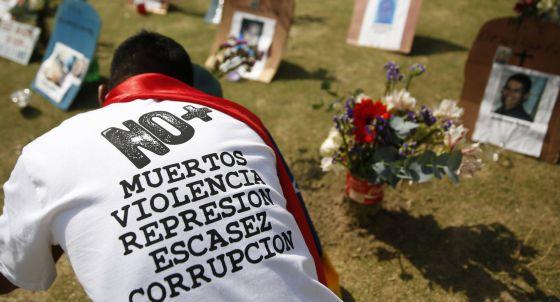 Un ciudadano delante de las tumbas de los fallecidos por la violencia en Venezuela.