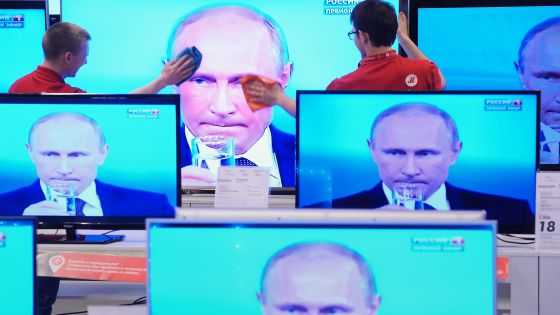 Empleados de una tienda limpian una pantalla de televisión durante una intervención televisiva del presidente Vladímir Putin, el jueves en Moscú.