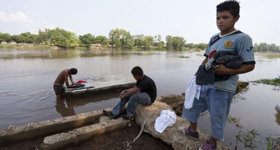 Migrantes hondureños lavan su ropa en la frontera de México y Guatemala.