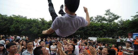 Estudiantes de instituto lanzan al aire a su profesor después de los exámenes de acceso a la universidad celebrados en China este fin de semana.