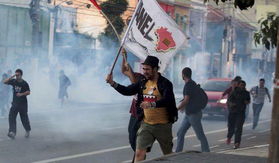 Manifestantes corren enate el lanzamiento de gases lacrimógenos.