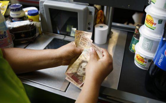 Una cajera cuenta dinero en un súper de Caracas.