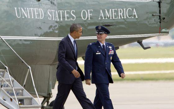 Obama, este jueves, junto a un coronel antes de subir al avión presidencial.