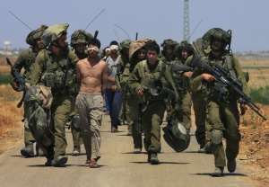 Soldados israelíes escoltan a un grupo de palestinos detenidos, cerca de Kissufim