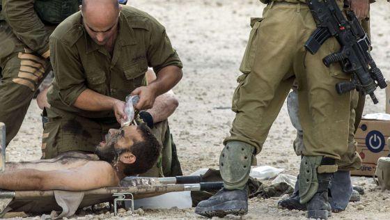 Soldados israelíes evacúan a un herido.